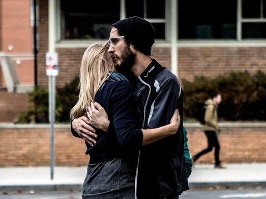 Alan Plotts embraces his wife, Elizabeth Riter, a student