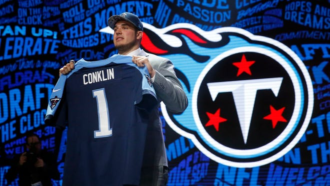 Jack Conklin holds a Titans jersey after being selected in the first round.