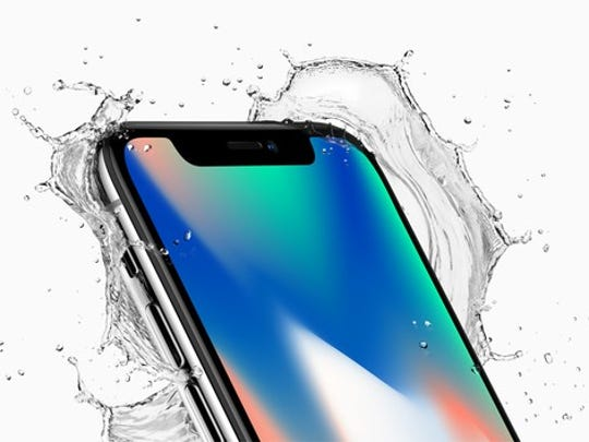 An iPhone X with water splashing around the face.