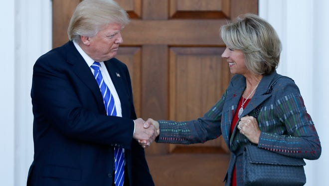 Donald Trump and Betsy DeVos shake hands after her interview Saturday.