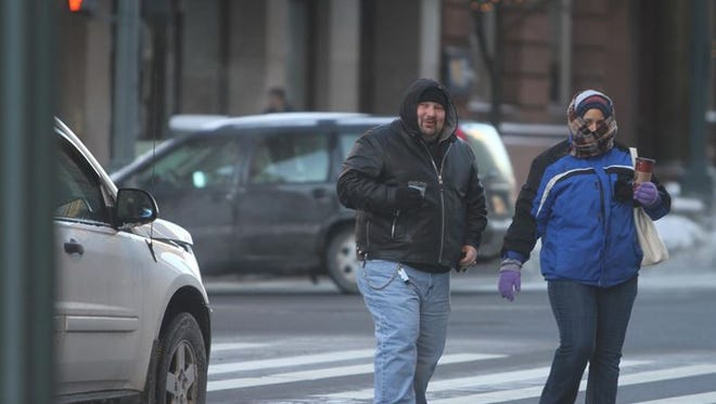 Anthony Lappetito and Tabbatha Campbell cross Main Street at State Street in downtown Rochester on Tuesday.