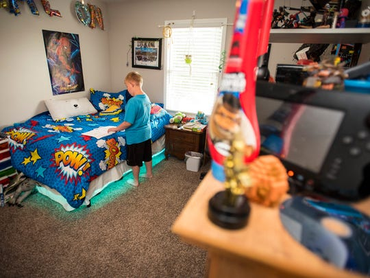 Linkyn Oliver, 9, looks at a comic book he drew about