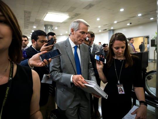 Reporters ask Sen. Rob Portman questions as he walks