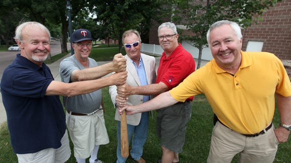 Terry Crandall (left to right), Dave Kemp, Brad Shaeffer, Pat Dunn and Andy Siverston stand where home plate used to be on the property of All Saints School.