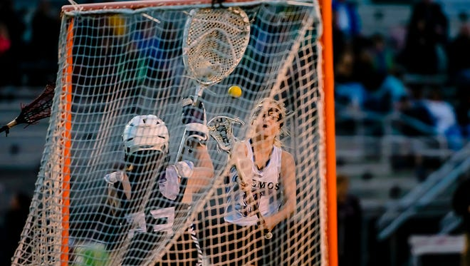 Alyssa Karber, right, of Okemos gets off a shot at the Haslett-Williamston goalie, Autumn Cole.