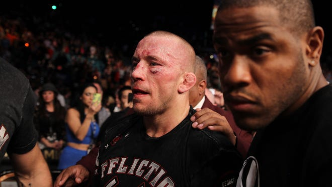 Georges St. Pierre, of Canada, exits the octagon following a UFC 167 mixed martial arts championship welterweight bout against Johny Hendricks on Saturday, Nov. 16, 2013, in Las Vegas. St. Pierre won by split decision.