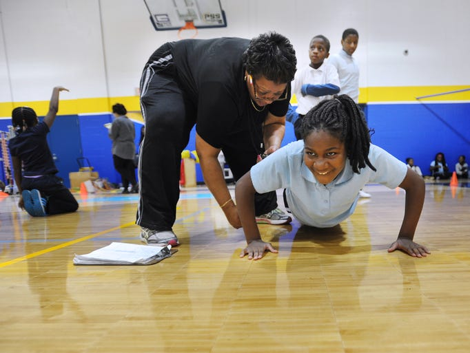 Physical Education Teacher Ann Turner, left, helps