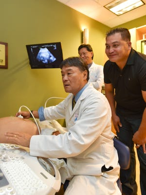 Dr. Greigh I. Hirata, left, performs an ultrasound exam as James B. Doyle looks on  at Dr. Shieh's Clinic in Tamuning on Sept. 6.