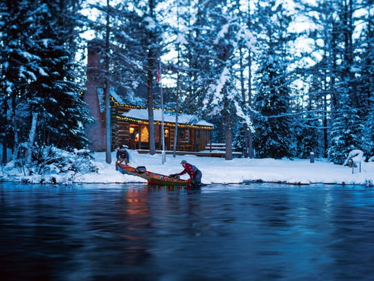 William Saputo of Rochester and Donn Vidosh of Petoskey serve as models for Cabela's in this photo taken the Au Sable River near Grayling with Saputo's log cabin lit up in the background.