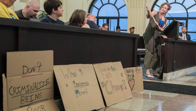 Battle Creek resident Taryn Vitale shows cardboard signs she and her daughter made to express their opposition to the panhandling ordinance.