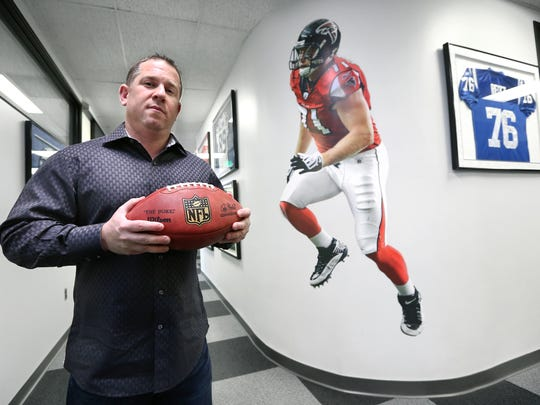 "Andrew ""Buddy"" Baker is the President/CEO of Exclusive Sports Group, LLC stands among several different client memorabilia in his downtown office at Pan Am Plaza on Wednesday, Feb. 11, 2015."