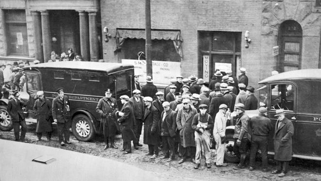 """Police and people in front of the S.M.C. Cartage Co. garage in Chicago on Feb. 14, 1929, following the St. Valentine's Day massacre. Five henchmen from mobster Al Capone's gang killed seven members of George """"Bugs"""" Moran's gang inside the garage."""