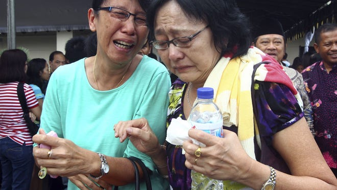 Relatives of passengers of AirAsia Flight 8501 cry after visiting the crisis center at Juanda International Airport in Surabaya, East Java, Indonesia, Wednesday. A massive hunt for the victims of the airliner resumed in the Java Sea on Wednesday, but wind, strong currents and high surf hampered recovery efforts as distraught family members anxiously waited to identify their loved ones.