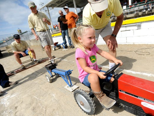 Josie Mallow, 3, of Frankfort starts to pedal hard during the Ross County Fair Kiddie Tractor Pull on Saturday. Children were divided into four groups based on weight and tried to see how far they could pedal a sled with added weight.
