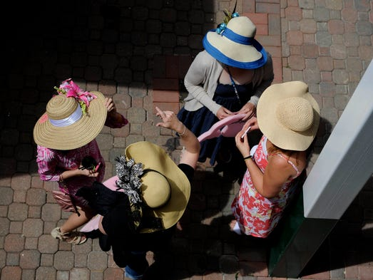 A collection of hats (with women underneath) meet at Churchill Downs prior to the Kentucky Derby.