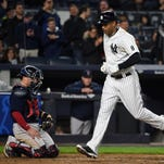 New York Yankees Aaron Hicks crosses home plate in front of Boston Red Sox catcher Christian Vazquez after hitting a solo home run off Red Sox starting pitcher Rick Porcello in the seventh inning of a baseball game, Friday, May 6, 2016, in New York.