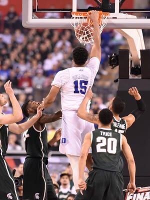 Duke's Jahlil Okafor throws down a dunk past MSU's Matt Costello, Branden Dawson, Denzel Valentine and Travis Trice