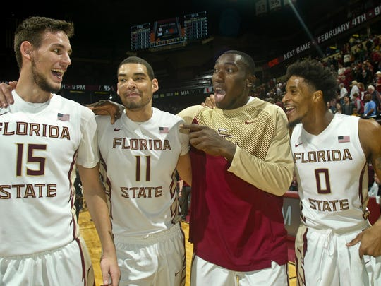 Florida State Seminoles centers Boris Bojanovsky (15), Kiel Turpin (11), Michael Ojo (50) and forward Phil Cofer (0) celebrate after their game against the Miami Hurricanes at the Donald L. Tucker Center.