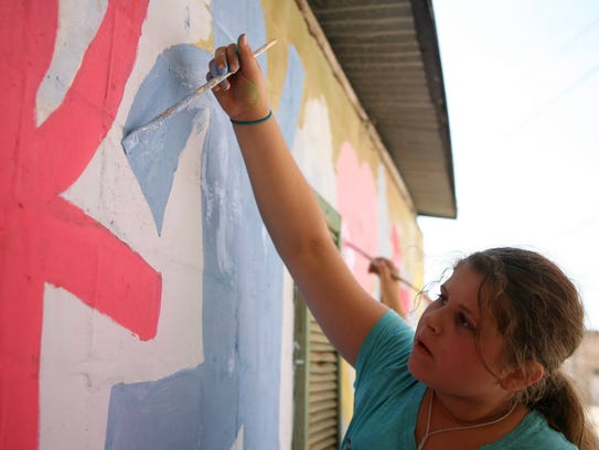 Helen Herndon paints in Art Alley with other Art Outside