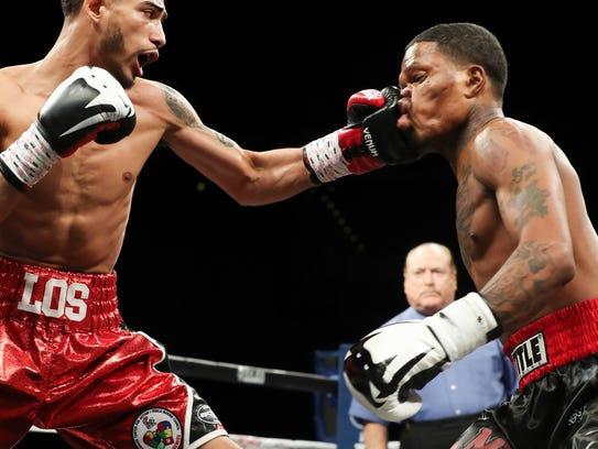 Louisville's Carlos Dixon, left, lands a punch against