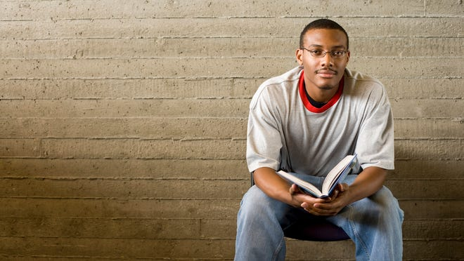 Young man reads and studies in a library