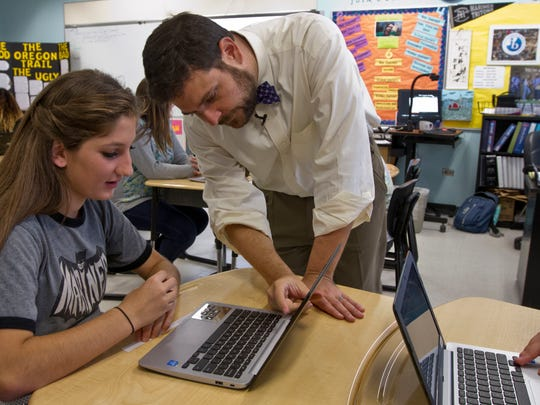Mariner Middle School history teacher Jim Kroll assists one of his 8th grade US history class students, Isabelle Ryan while working on a calss assignment Tuesday morning (4/9/15). Kroll is a 2015 Golden Apple winner.