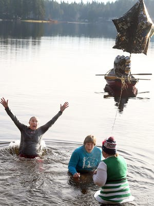 Plunge event organizer Lisa Ballou, left, celebrates the last two plungers at the New Year's plunge into Wildcat Lake. They are Liz Angeleri, center, of Chehalis, and Kathy White, right, of Olympia