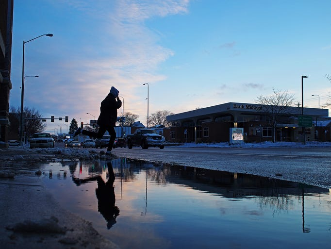 A pedestrian jumps over a puddle of melted snow while