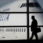 In this file photo made Jan. 21, 2010, a passenger walks past a Delta Airlines 747 aircraft.