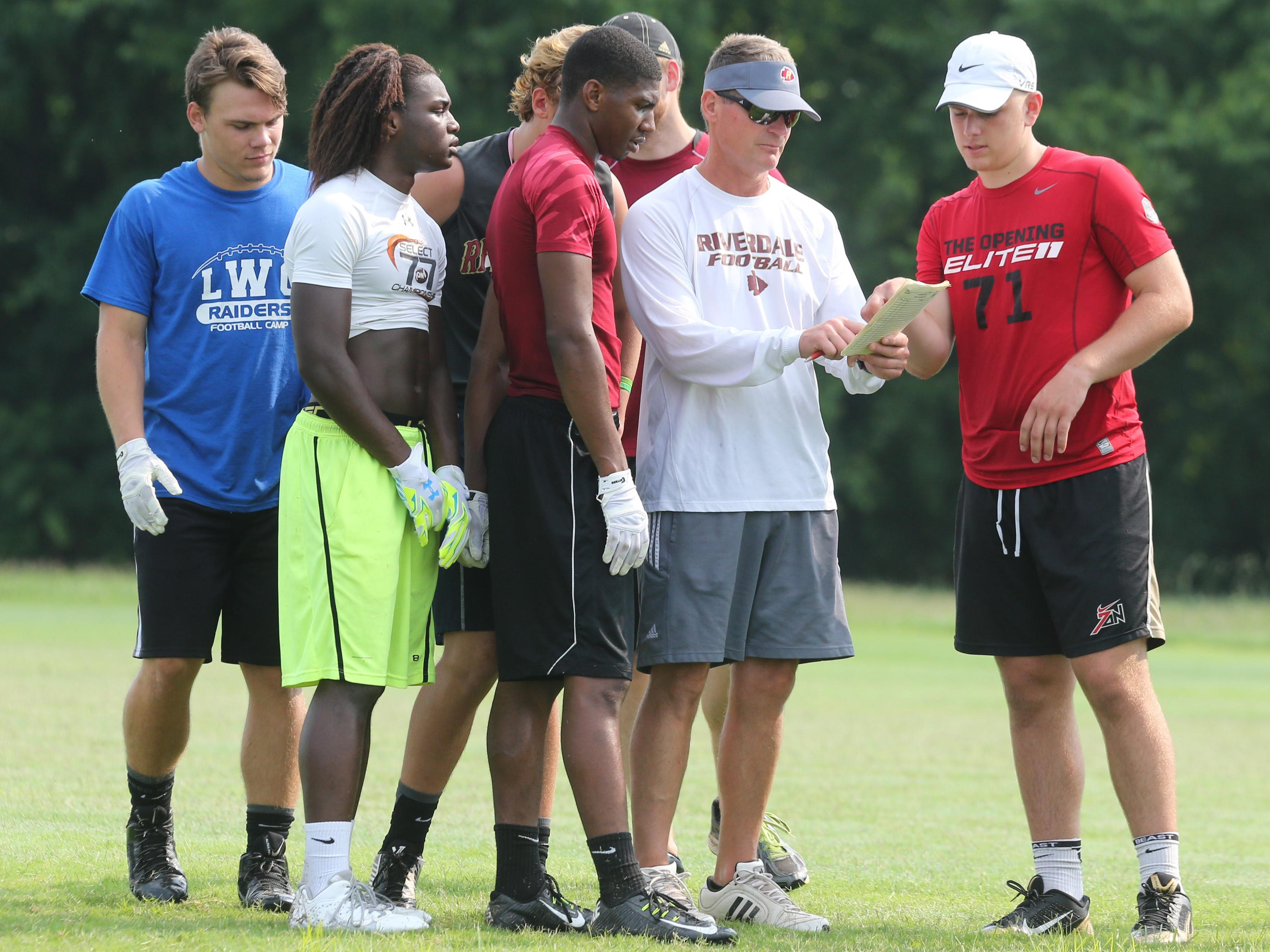 Riverdale football coach Ron Aydelott goes over an offensive play during a 7-on-7 practice Monday.