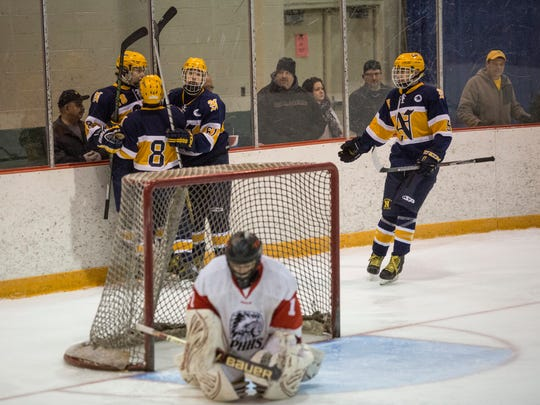 Northern players celebrate scoring a goal behind the