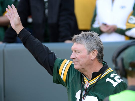 Lynn Dickey waves to the crowd as he is introduced at halftime of the Packers' game against the New York Jets at Lambeau Field in 2014.