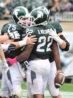 MSU teammates Benny McGowan (75) celebrate with running back Delton Williams (22) after Williams' touchdown in the second quarter. Michigan State vs Indiana at Spartan Stadium in East Lansing, Mich. on Oct. 24, 2015. (Robin Buckson / Detroit News)