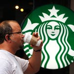 In this July 11, 2013  file photo, a man drinks a Starbucks coffee in New York.