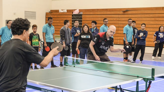 2000 Sydney Games Olympian Brett Clarke, playing right, and Guam Table Tennis Federation President James Ji, demonstrate playing fundamentals to students during a table tennis clinic at Southern High School in Santa Rita on Thursday, Dec. 10.