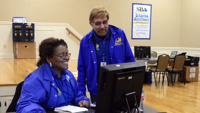 SBA disaster assistance members Euro Atencio, right, and Anita Bing work together to help tornado victims in the C.E. Roy Community Center on Friday. Federal disaster relief officials are urging tornado survivors to stop by one of three local Disaster  Recovery Centers to apply for FEMA grants and Small Business Administration loans.