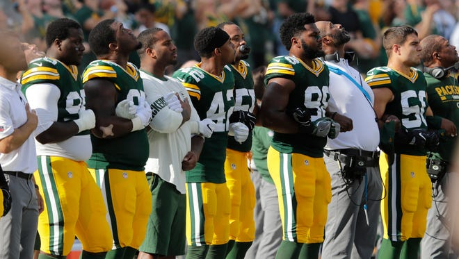 Green Bay Packers players lock arms during the national anthem before their game against the Cincinnati Bengals  on Sunday, Sept. 24, 2017, at Lambeau Field in Green Bay, Wis. NFL players responded in full force Sunday after President Trump repeatedly called for swift punishment against those who chose to protest by not standing during the national anthem.