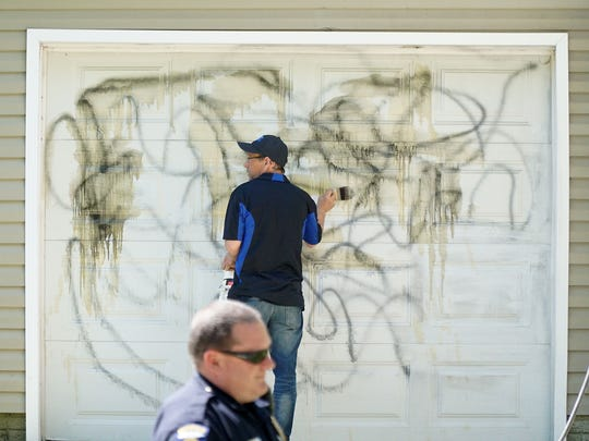 Brian Gladden cleans graffiti off a garage door at 621 King Street as Mansfield police sergeant John Ahles keeps him safe Monday morning.