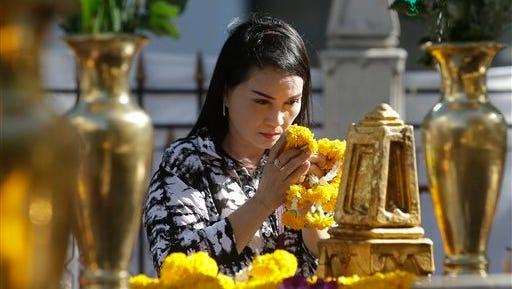 In this Aug. 19, 2015, photo, a woman prays at the Erawan Shrine at Rajprasong intersection in Bangkok, Thailand, the day after a deadly explosion. In Bangkok this week, struggling in the aftermath of an unexplained bombing that left 20 people dead and more than 120 injured, the explosion made starkly clear that cities are still wrestling with the question: How do we keep ourselves safe?   (AP Photo/Sakchai Lalit)