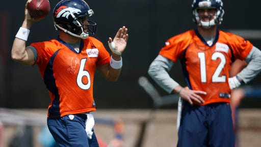 Denver Broncos quarterback Mark Sanchez, front, throws a pass as rookie quarterback Paxton Lynch looks on during NFL football practice Tuesday, May 31, 2016, at the team's headquarters in Englewood, Colo. (AP Photo/David Zalubowski)