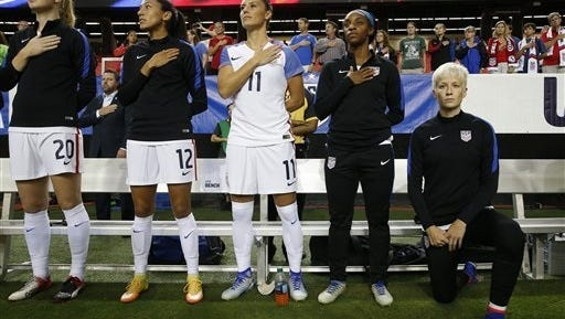 USA's Megan Rapinoe, right, kneels next to teammates as the U.S. national anthem is played before an exhibition soccer match against Netherlands on Sunday.