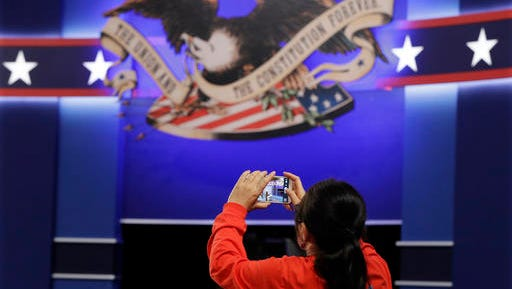 A volunteer takes a photos of the stage in the debate hall as preparations are made for the second presidential debate between Republican presidential nominee Donald Trump  Democratic presidential nominee Hillary Clinton at Washington University in St. Louis, Saturday, Oct. 8, 2016. (AP Photo/Julio Cortez)