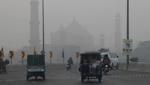 Motorists drive through a road close to historical Badshahi mosque while dense smog engulf the neighborhood of Lahore, Pakistan, Saturday, Nov. 5, 2016. Thick smog has engulfed several cities in central Pakistan for a few days, causing, breathing problems, road accidents and disruption of flight and train scheduled as well as the closure of the sections of the main motorways.