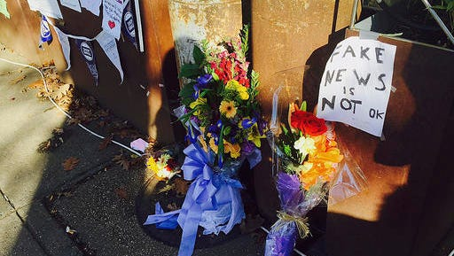 FILE - In this Friday Dec. 9, 2016 file photo, flowers and notes left by well-wishers are displayed outside Comet Ping Pong, the pizza restaurant in Washington. There's at least a slice of good news for a pizza restaurant in the nation's capital that has been the target of fake news stories linking it to a child sex trafficking ring. In almost a week since an armed man arrived at Comet Ping Pong to investigate the conspiracy, neighbors and patrons have responded by bringing homemade signs, flowers and their pizza-purchasing power to the store.
