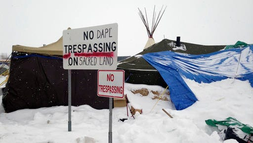 Signs are displayed Wednesday, Jan. 25, 2017, in the bitter weather at an encampment near Cannon Ball, N.D., to protest the Dakota Access pipeline. Some protesters are vowing to stay in the camp despite a Trump administration order that seeks to expedite the pipeline's completion.