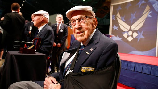"""FILE – In this April 18, 2015, file photo, two members of the Doolittle Tokyo Raiders, retired U.S. Air Force Lt. Col. Richard """"Dick"""" Cole, seated front, and retired Staff Sgt. David Thatcher, seated left, pose for photos after the presentation of a Congressional Gold Medal honoring the Doolittle Tokyo Raiders at the National Museum of the U.S. Air Force at Wright-Patterson Air Force Base in Dayton, Ohio. Cole, co-pilot of the Doolittle Tokyo Raiders' lead plane and a fly-over by vintage B-25 bombers will be part of Ohio events April 17-18, 2017 for the 75th anniversary of the daring attack that helped turn the tide of World War II. Cole said it will be a somber moment when he toasts fellow Raider, Thatcher, who died in 2016. (AP Photo/Gary Landers, File)"""