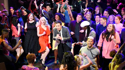 "In this April 15, 2017 photo released by NBC, host Jimmy Fallon, center, performs during the live opening number on ""Saturday Night Live,"" in New York. The network's telecast last weekend, with musician Harry Styles and  Alec Baldwin and Melissa McCarthy delivering their hit impersonations of Donald Trump and Sean Spicer, was seen by 7.87 million people this weekend, or 21 percent more than the previous week's telecast, the Nielsen company said."