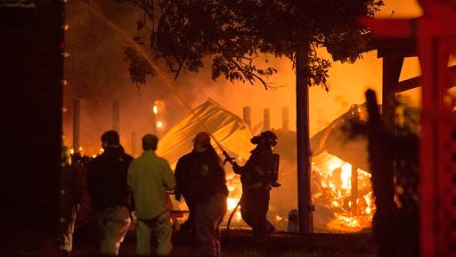 Firefighters work to contain a fire at the Mississippi Agriculture and Forestry Museum in Jackson, Mississippi, Thursday, Nov. 13, 2014, as museum employees and others look on.  (AP Photo/The Clarion-Ledger, Joe Ellis)