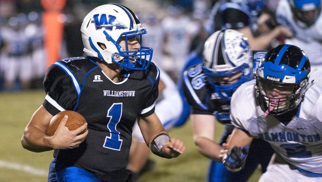 Williamstown's quarterback Rich Stanzione, left, runs the ball during Friday's game against Hammonton. The Braves prevailed over previously unbeaten Hammonton.