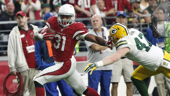 Arizona Cardinals RB David Johnson runs after a catch while tackled by Green Bay Packers LB Jake Ryan during the second quarter in NFL action December 27, 2015 in Glendale, Ariz.